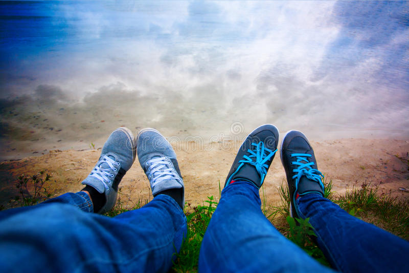 Dois pares de pés na costa do lago. céu foto de stock