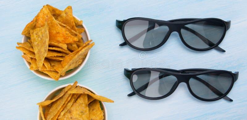 dois pares dos vidros 3D em uma tabela azul, ao lado das cubetas dos nachos fotos de stock royalty free