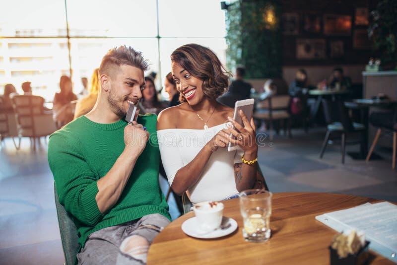 Dois pares felizes da raça misturada que têm o divertimento na cafetaria fotos de stock