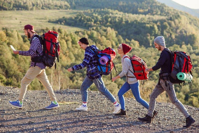 Dois pares felizes que andam nas montanhas com o mapa Homem caucasiano novo com o mapa que escolhe a dire??o certa Curso imagem de stock