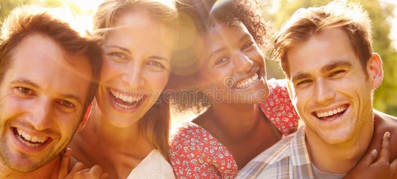 Dois pares felizes que sorriem à câmera fora, perto acima imagem de stock