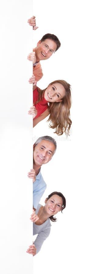 Dois pares felizes que sustentam uma placa vazia fotografia de stock