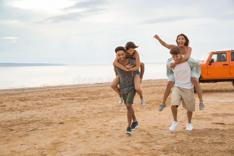Dois pares felizes que têm o divertimento junto na praia fotos de stock royalty free