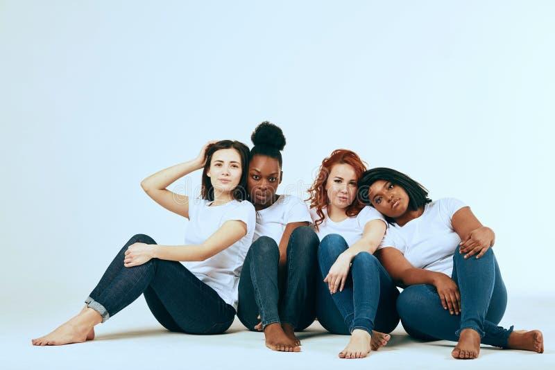 Dois pares multiculturais de mulheres na vista ocasional feliz junto no branco fotografia de stock