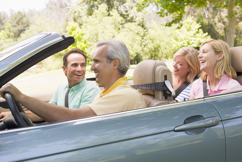 Dois pares no sorriso convertível do carro imagem de stock royalty free