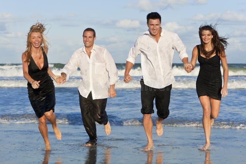 Dois pares, tendo o divertimento funcionar na praia foto de stock royalty free