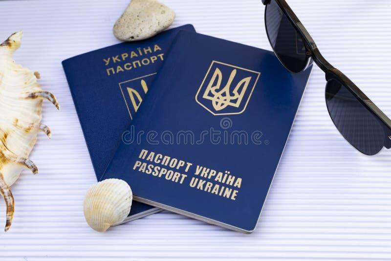 Dois passaportes ucranianos com óculos de sol e conchas do mar em c branco imagens de stock