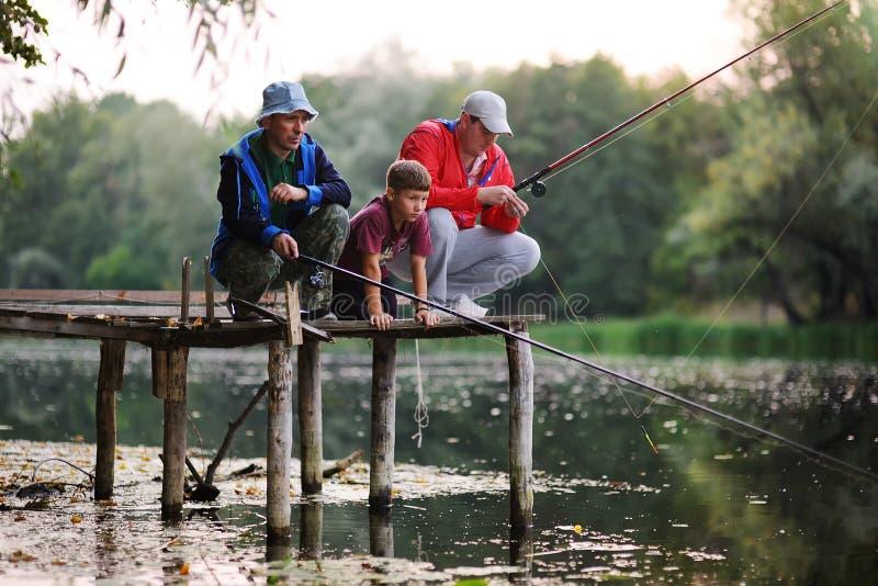Dois peixes da captura dos pescadores que estão na ponte imagem de stock
