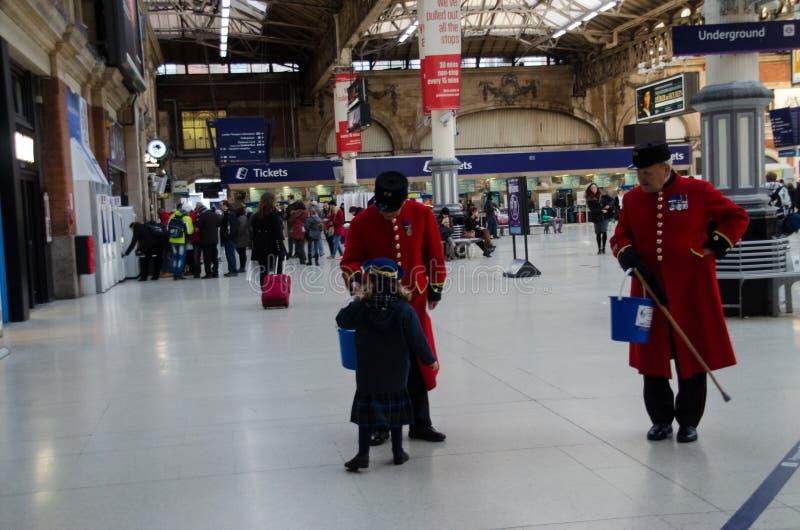 Dois pensionista de Chelsea em Victoria Station em Londres, Reino Unido imagem de stock royalty free