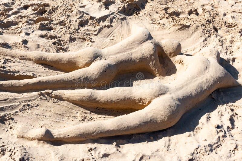 Dois pessoas da escultura da areia na praia arenosa de Papagayo na ilha de Lanzarote, Ilhas Canárias, Espanha fotos de stock royalty free