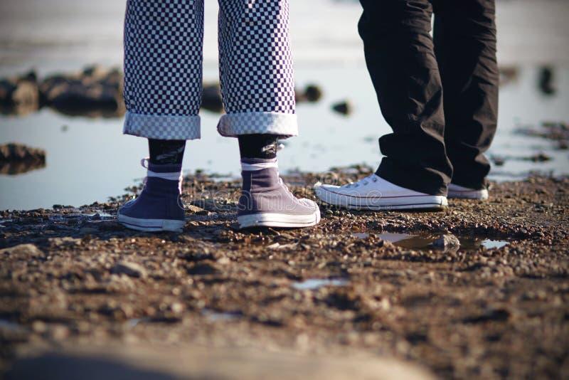 Dois pessoas nas sapatilhas estão na praia imagem de stock