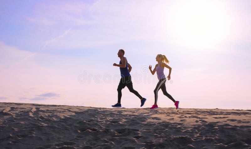 Dois pessoas que movimentam-se no por do sol fotografia de stock royalty free