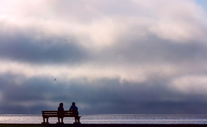 Dois pessoas que sentam-se em um banco da rua e que olham o por do sol dramático foto de stock royalty free