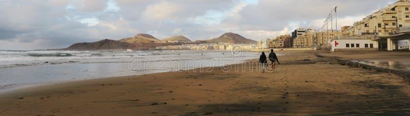 Dois pessoas que tomam uma caminhada no sol de nivelamento na praia em Las Palmas de Gran Canaria imagem de stock