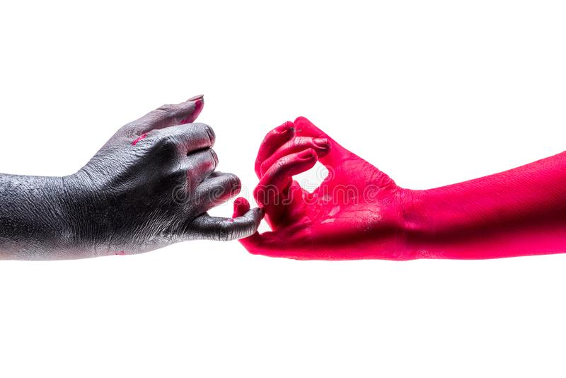 Dois pessoas tocam com cuidado nos dedos pequenos de cada um, mãos coloridas em cores diferentes Conceito da guerra e da paz fotos de stock