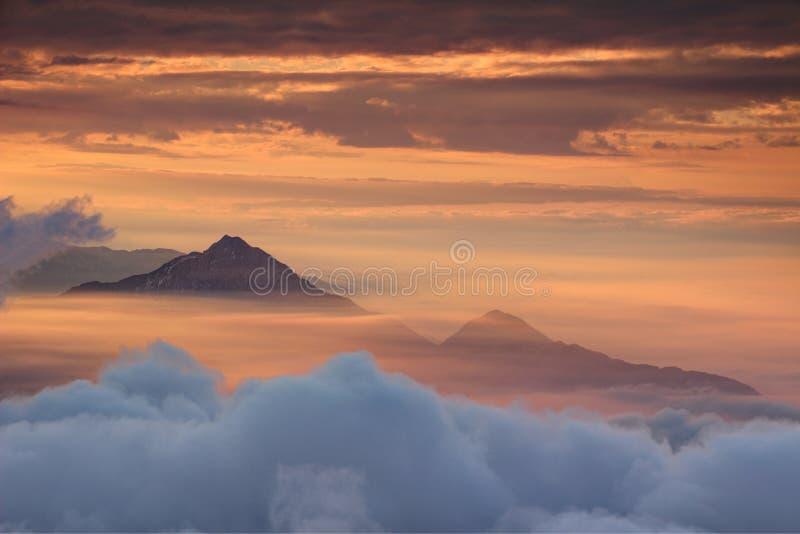 Dois picos cônicos acima da névoa alaranjada da manhã translúcida do outono fotos de stock royalty free