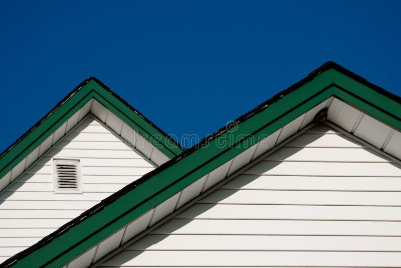 Dois picos do telhado da casa da quinta de encontro a um céu azul foto de stock