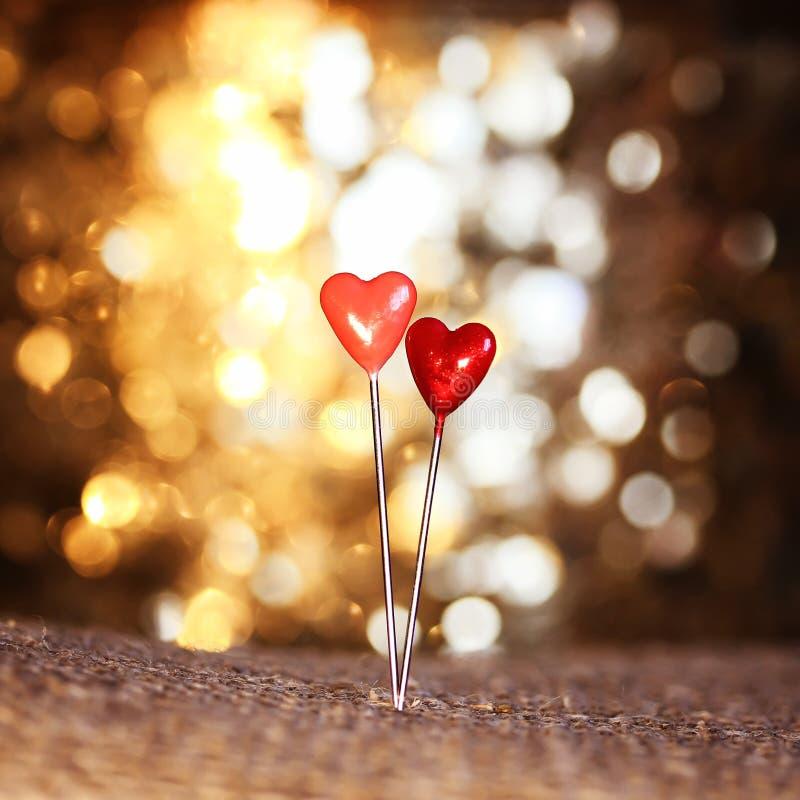 Dois pinos afiados sob a forma dos corações vermelhos colaram na serapilheira sobre fotografia de stock