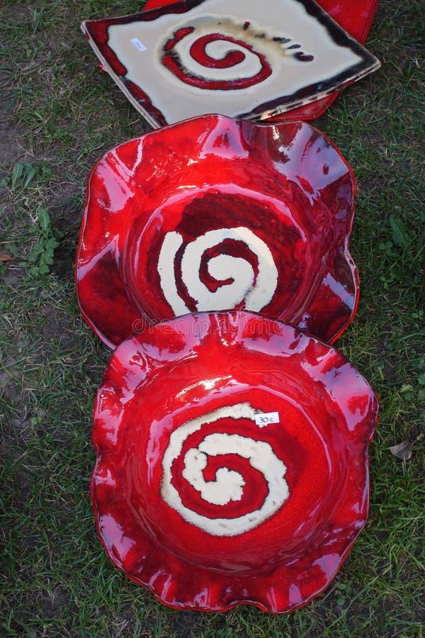 Dois placas cerâmicas vermelhas com espiral branca um descanso tirado na grama e muito típicos de Galiza, Espanha fotos de stock royalty free