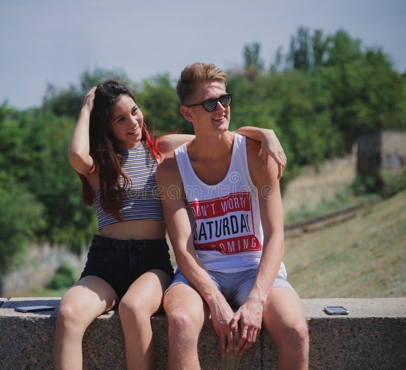Dois positivos, adolescentes frescos que sentam-se em um fundo natural Pares românticos bonitos em um parque da cidade Conceito r imagem de stock royalty free