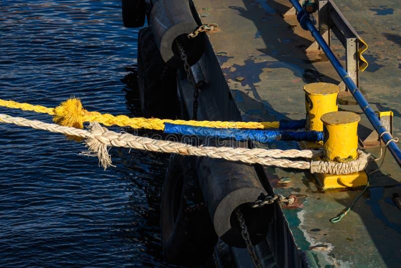 Dois postes de amarração amarelos em uma doca comercial com as cordas da amarração unidas, dia ensolarado, os amortecedores do ág imagem de stock royalty free