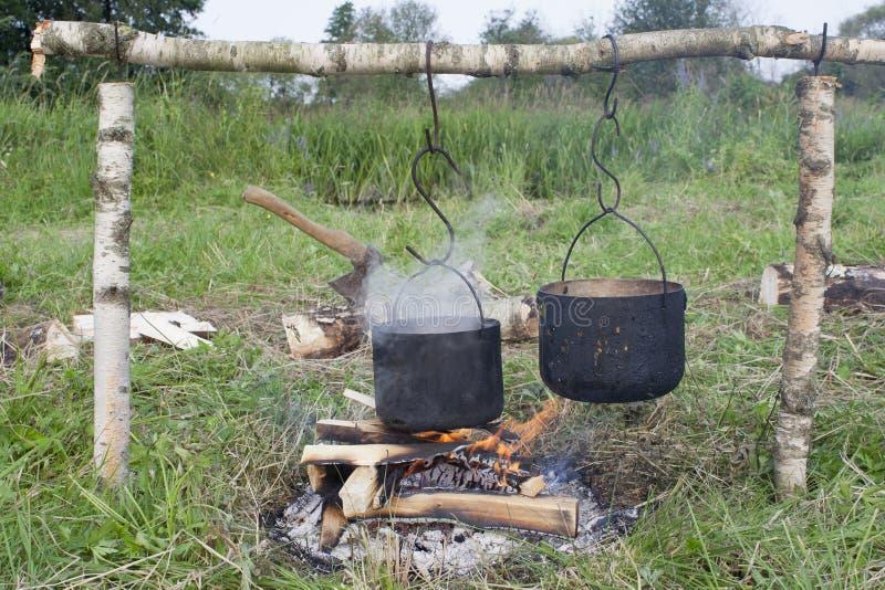 Dois potes de água estão pendurados sobre o fogo fotografia de stock royalty free