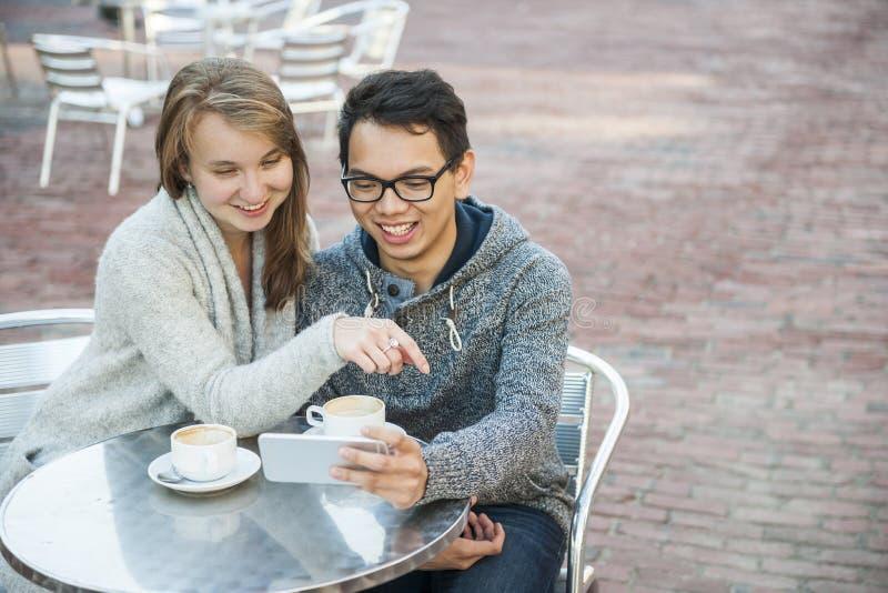 Dois povos com o smartphone no café imagens de stock