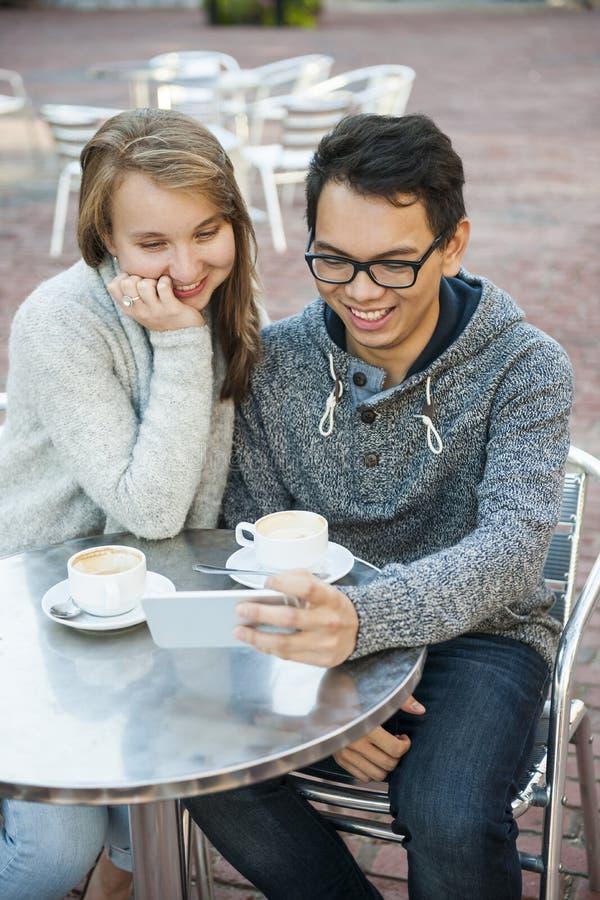 Dois povos com o smartphone no café foto de stock