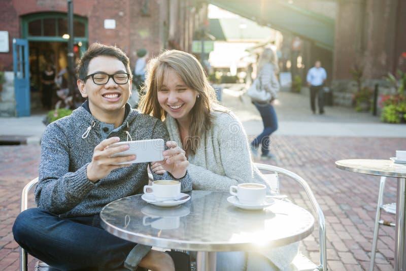 Dois povos com o smartphone no café imagem de stock