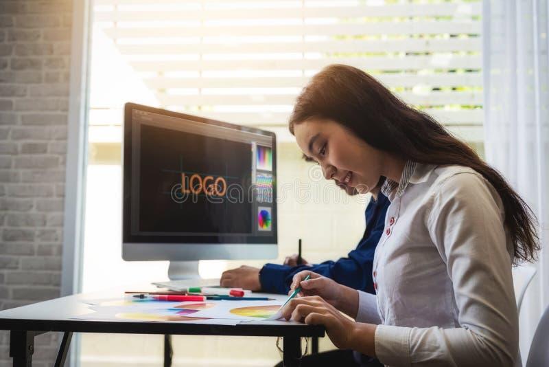 Dois povos criativos gráficos do desenhista que trabalham sobre o projeto do Web site com computador e o estilo seleto da cor par imagem de stock