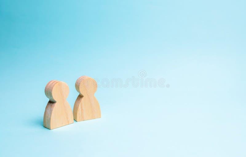 Dois povos estão junto e falam Duas figuras de madeira dos povos conduzem uma conversação em um fundo azul uma comunicação, fotos de stock