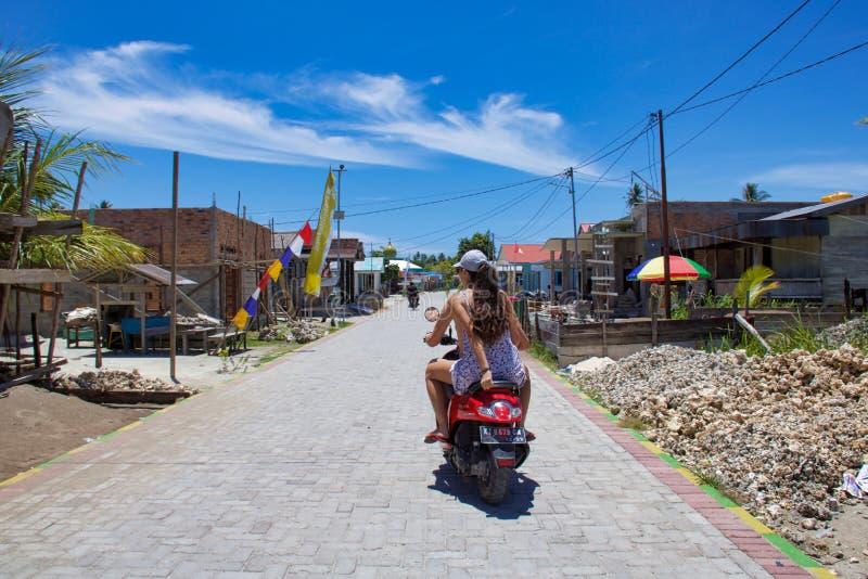 Dois povos europeus montam a rua de uma vila pelo velomotor fotos de stock royalty free
