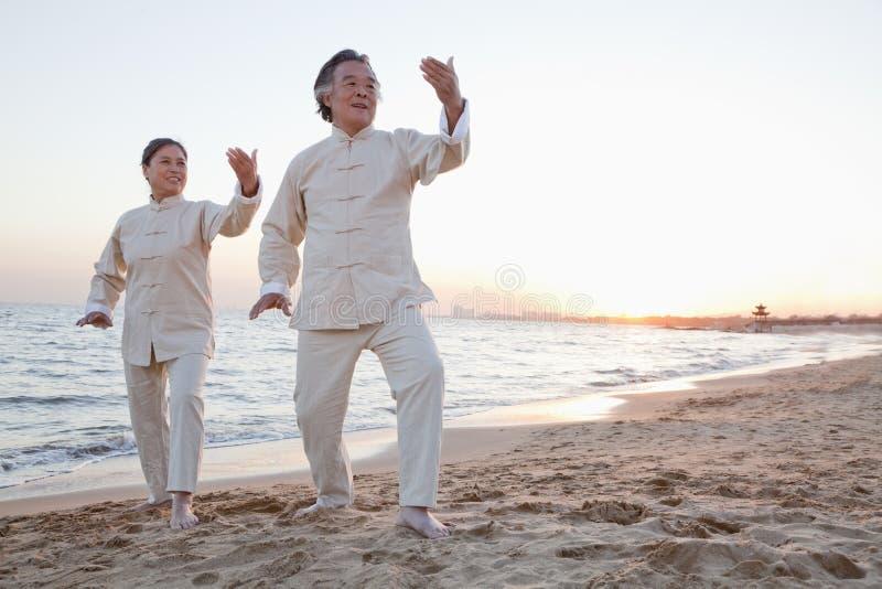 Dois povos mais idosos que praticam Taijiquan na praia no por do sol, China fotos de stock royalty free