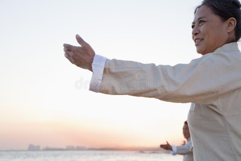 Dois povos mais idosos que praticam Taijiquan na praia no por do sol, China fotos de stock
