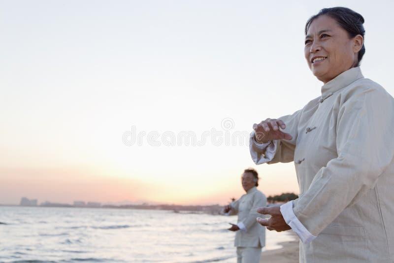 Dois povos mais idosos que praticam Taijiquan na praia no por do sol, China foto de stock
