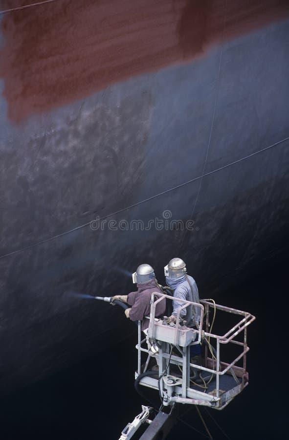 Dois povos que estão no guindaste bucket o grande navio de pintura foto de stock