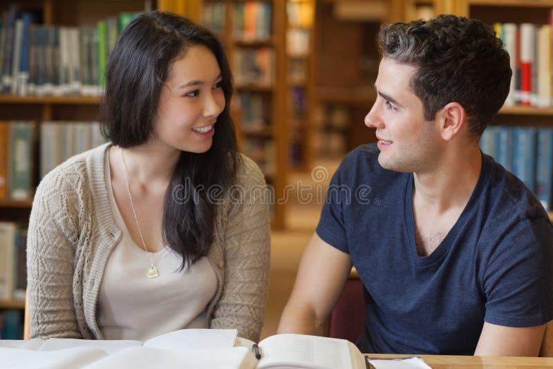 Dois povos que estudam em uma biblioteca fotografia de stock royalty free