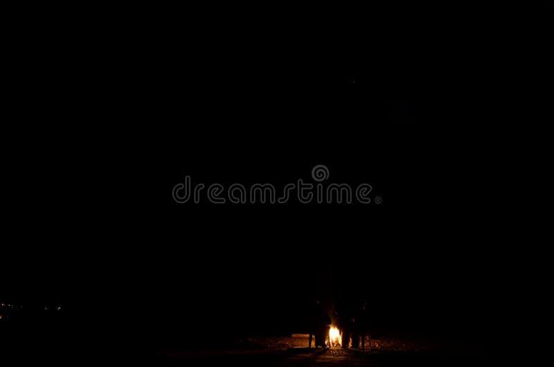 Dois povos que sentam-se em torno da fogueira de aquecimento na região selvagem fria do outono foto de stock