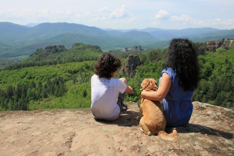 Dois povos que sentam-se em uma rocha altamente nas montanhas fotos de stock