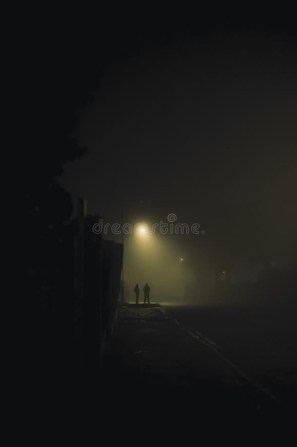 Dois povos sob a lâmpada de rua foto de stock