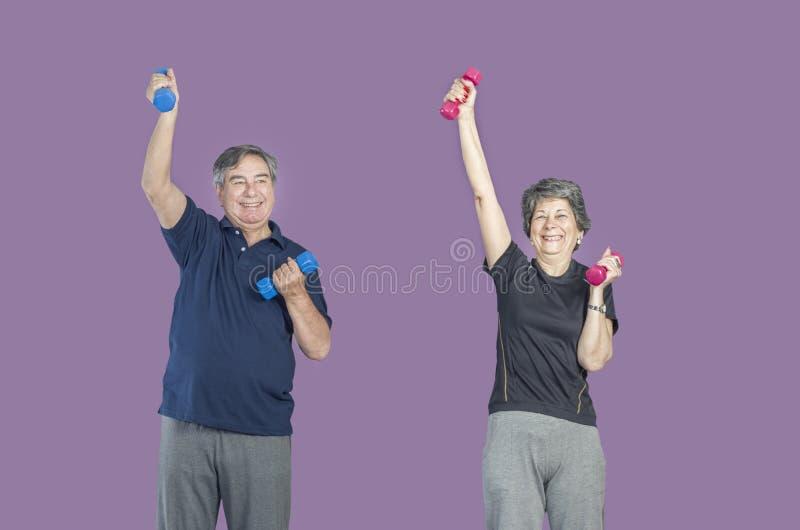 Dois povos superiores em uma classe do gym que faz o exercício de Pilates levantam wei imagem de stock royalty free