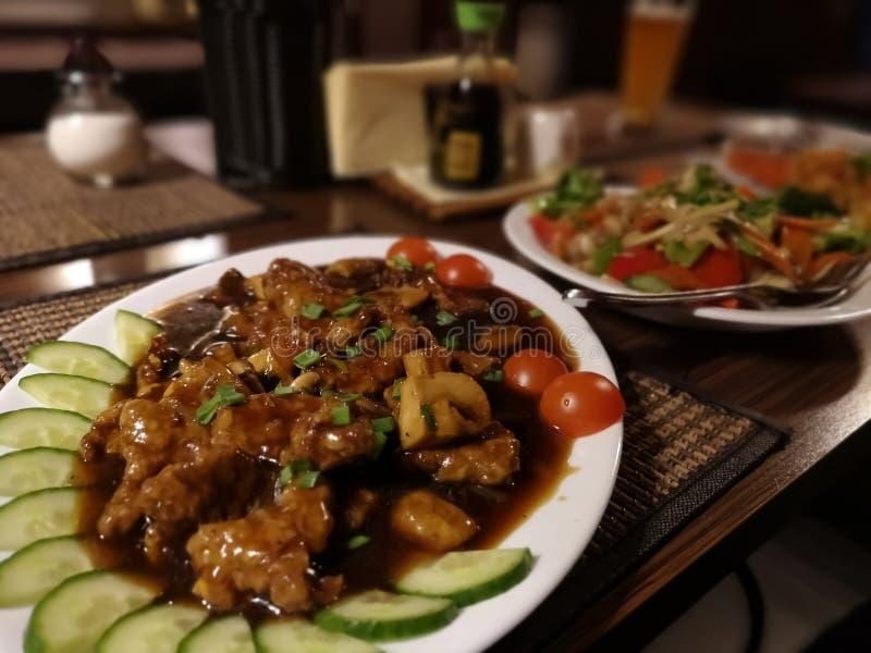 Dois pratos orientais com carne, galinha, tomates, cenouras, pimenta vermelha e macarronetes de arroz imagem de stock