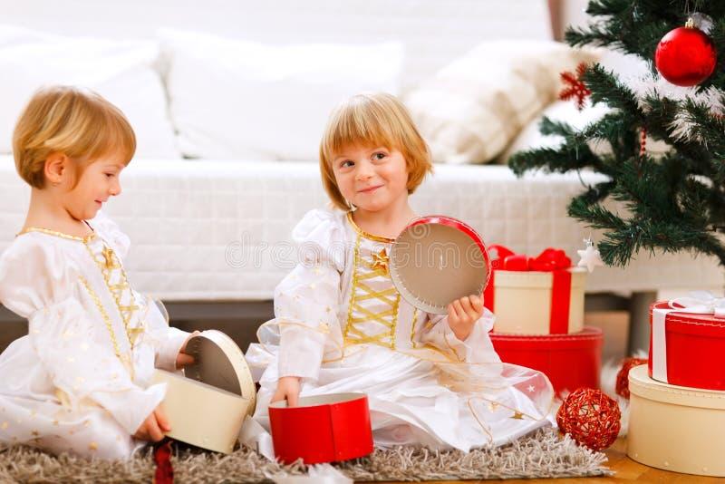 Dois presentes da abertura da menina dos gêmeos aproximam a árvore de Natal fotos de stock royalty free