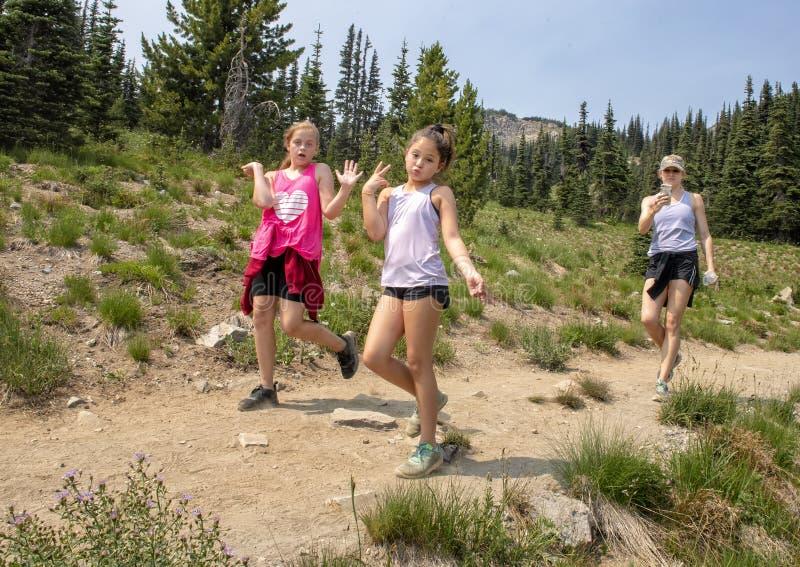 Dois primos fêmeas e uma mãe que tem o divertimento em uma caminhada na montagem Rainier National Park, Washington fotos de stock