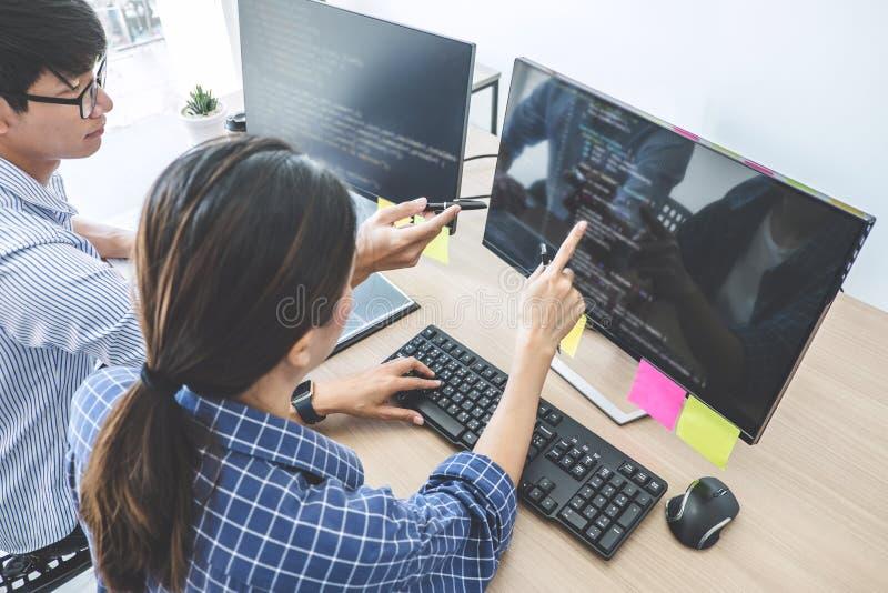 Dois programadores profissionais que cooperam na programação e no Web site tornando-se que trabalham em um software desenvolvem o fotografia de stock