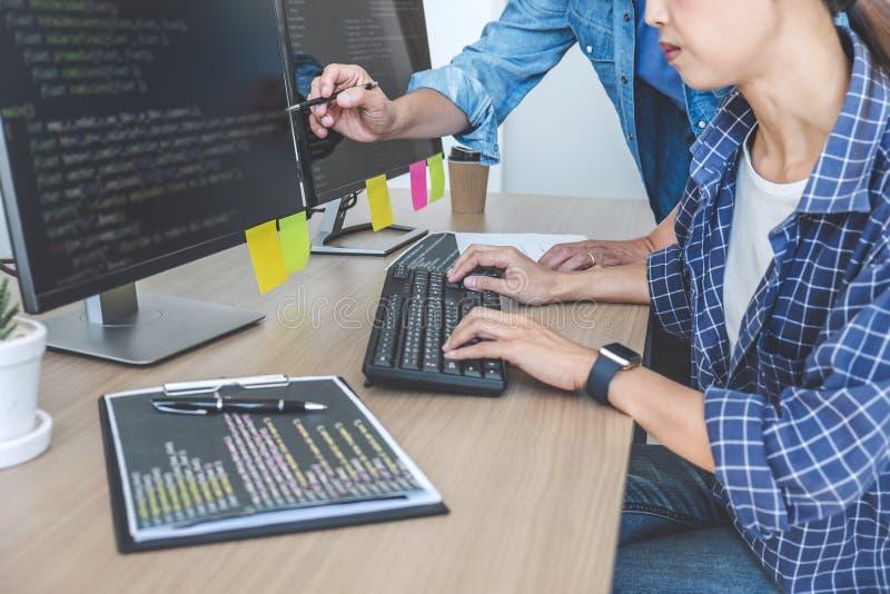 Dois programadores profissionais que cooperam na programação e no Web site tornando-se que trabalham em um software desenvolvem o fotografia de stock royalty free