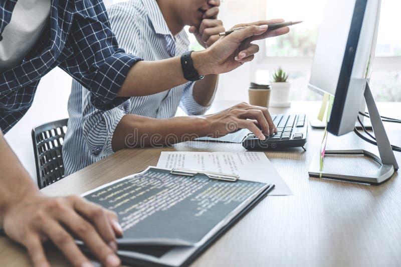 Dois programadores profissionais que cooperam na programação e no Web site tornando-se que trabalham em um software desenvolvem o imagens de stock