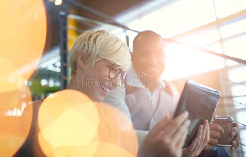 Dois proprietários empresariais pequenos millenial criativos que trabalham na estratégia social dos meios usando uma tabuleta dig fotografia de stock
