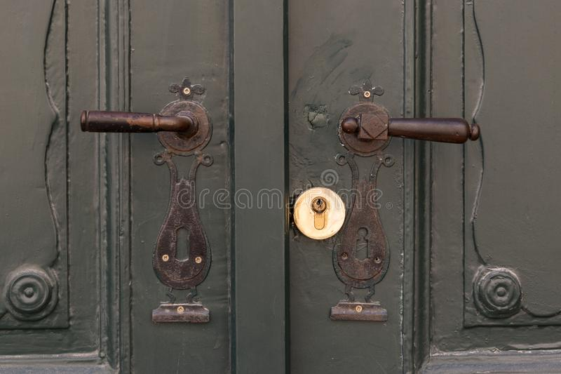 Dois puxadores da porta velhos do metal em portas de madeira verdes fotos de stock royalty free