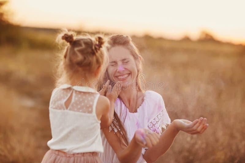 dois que jogam com a cor no festival do holi a mãe e a filha são jogadas na natureza das cores foto de stock royalty free